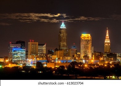 Brightly lit Cleveland Ohio under a full moon rising through a wisp of clouds
