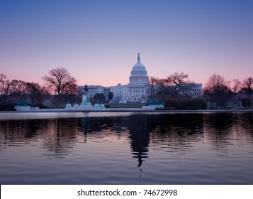 Brightly lit dawn sky behind the illuminated dome of the Capitol in Washington DC with the pool and statues