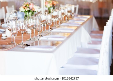 Brightly lit decorated table at wedding reception. Selective focus on glassware