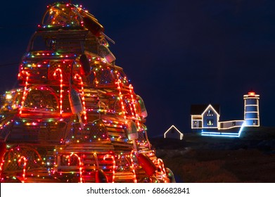 Brightly lit holiday tree made of lobster traps and fishing gear displays in front of lighted Nubble lighthouse for the Christmas season. A tradition along the New England seacoast.