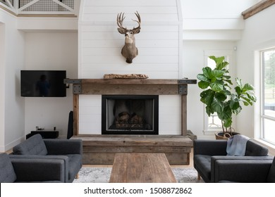 Brightly lit living room of a modern beach house or farmhouse. Featuring reclaimed wood and white walls.