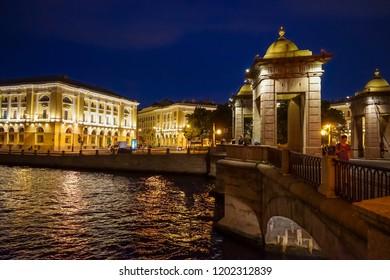 Brightly lit Lomonosov Bridge and Lomonosov Square at night in St. Petersburg. Russia
