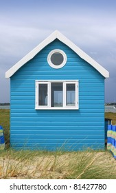A brightly painted blue wooden constructed beach hut set amongst sand dunes and grasses. located in Christchurch, Dorset UK.