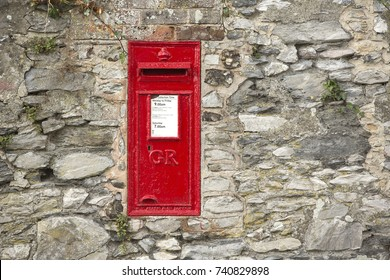 Brightly painted British red wall box set into an uneven stone wall. Vintage post box surviving from the era of King George VI circa 1936. GR cypher indicating the G for George and R for Rex.