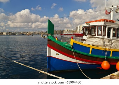 """Brightly painted fishing boats (""""luzzi"""") in harbor, on the island of Malta. The boats carry the """"Eyes of Osiris"""" to prevent ill-fortune."""