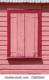 Brightly pink painted wooden window shutters