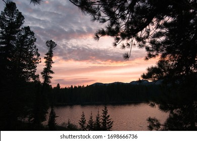 Brightly rochy sunset on a lake surrounded by trees and mountains in the distance.