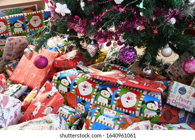 Brightly wrapped presents underneath a colorful decorated Christmas tree