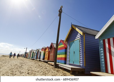 Brighton Beach, Australia: March 31, 2017: A tourist takes a photo of his girlfriend by the colorful beach huts on Brighton Beach in Melbourne. Unidentified people walk down the beach.