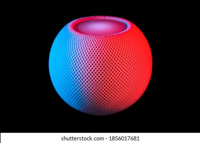 Brighton, East Sussex, UK - November 16 2020: HomePod mini smart speaker with Siri voice assistant by Apple in white, photographed on dark background