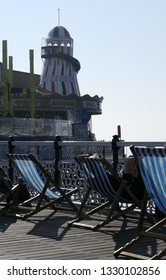 Brighton, East Sussex/England - February 27 2019 - people sitting in deckchairs in the sun on Brighton Palace Pier with a view of the fair during the hottest February in the UK on record
