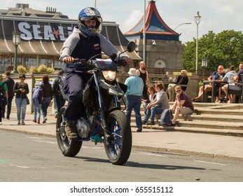 BRIGHTON ENGLAND 4th JUNE 2017: London to Brighton Classic Car Run 4.06.17 in Brighton: Man driving motorbike in motor helmet with sea life in background