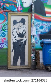 BRIGHTON, ENGLAND - CIRCA APRIL 2015: A photo of Banksy graffiti on the side of a pub in Brighton of two policemen kissing each other in a golden frame