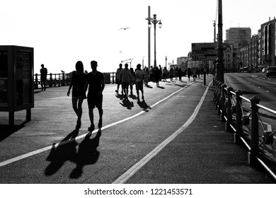 BRIGHTON, ENGLAND - JULY 9, 2018: Silhouette of pedestrians on the Brighton Marina walkway, Brighton, UK. Brighton is the most popular seaside destination in the UK for overseas tourists.