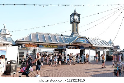 BRIGHTON, ENGLAND - JULY 9, 2018: Tourists in Brighton Palace Pier on Brighton beach, Brighton, UK. The pleasure pier opened in 1899 is a Grade II listed heritage structure in UK.