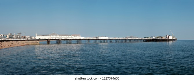 BRIGHTON, ENGLAND - JULY 9, 2018: Panoramic view of Brighton Pier from the west on Brighton beach, Brighton, UK. The pier opened in 1899 is a Grade II heritage listed structure in UK.