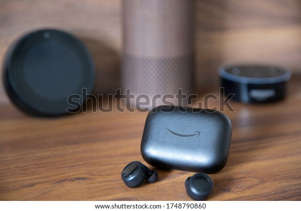 Brighton, England - June 4, 2020:  Echo Buds, the wireless earbuds released by Amazon in 2019 with Alexa + Bose Noise Cancelling support, picture on top of a wooden surface