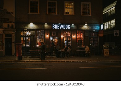 BRIGHTON, ENGLAND - October 26th, 2018: Night view of Brewdog brewery pub facade with people sitting and drinking beer in the terrace, viewed from the opposite sidewalk, in Brighton, Sussex, England.