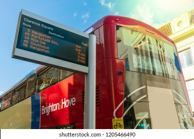 Brighton, England-1 October,2018: Bus stop with digital data board information sign for passenger with red two double decker buses in Brighton citytown with traffic in the morning