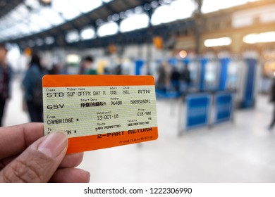 Brighton, England-18 October,2018: Hand holding UK Rail Return Ticket in Brighton & Hove train station with a group pasengers buying train tickets at self service ticket machine in background