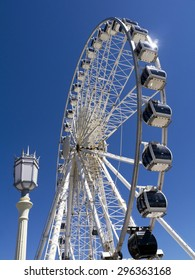 Brighton Eye Ferris Wheel; silhouetted against deep blue sky with street lamp in foreground