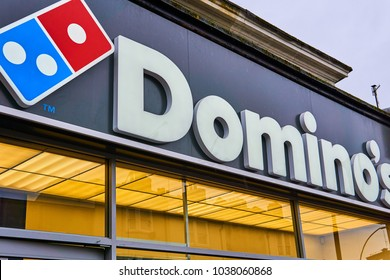 Brighton and Hove, East Sussex, England March 4th 2018 Domino's Pizza sign over the shop with the signature domino by the writing