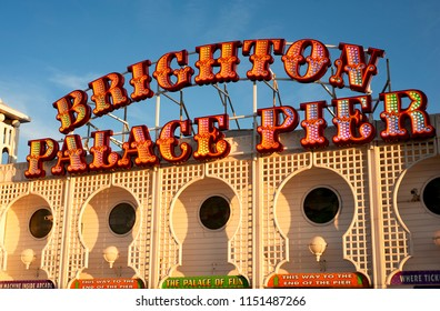 Brighton and Hove, Sussex, UK, July 2018. Brighton Palace Pier and its new sign lit up at sunset. The pier has been given a new name combining its two former names Brighton Pier and Palace Pier.