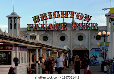 Brighton and Hove, Sussex, UK, March 2018. Tourists enjoying Brighton Palace Pier at the seaside in Brighton and Hove.  The famous pier is one of the U.K.'s most popular tourist attractions.