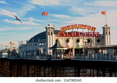 Brighton and Hove, Sussex, UK, March 2018. Brighton Palace Pier at the seaside of Brighton and Hove is lit up at sunset. The famous pier is one of the U.K.'s most popular tourist attractions