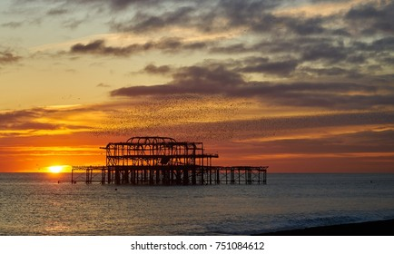 Brighton and Hove West pier ruins at sunset with thousands of Starlings flying in formation, called Murminations             - Shutterstock ID 751084612
