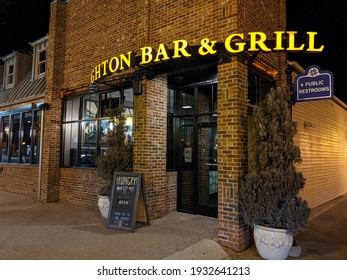 Brighton, Michigan, United States - March 8, 2021: Brighton Bar and Grill, the front of the building for the Brighton Bar and Grill along with a sign for public restrooms in downtown Brighton