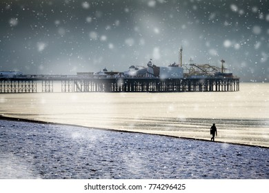 Brighton pier and seafront snowy scene: a lone walker passes by the famous landmark on the Sussex coast in this winter scene