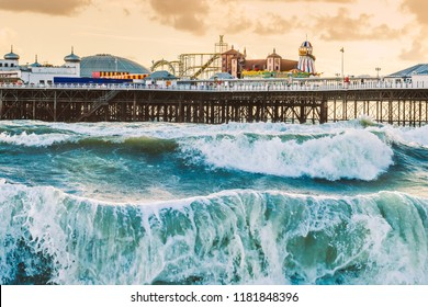 Brighton Pier, Brighton, Sussex, Britain on a storm evening at dusk as the sun is setting. There are high waves and surf on the beach