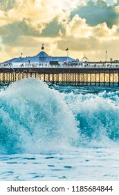 Brighton Pier, Brighton, Sussex, Britain on a stormy evening at dusk as the sun is setting. There are high waves and surf on the beach