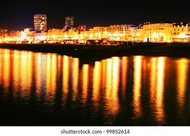 Brighton seafront at night, city lights reflecting in sea along coastline