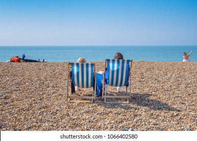 BRIGHTON, UK - APRIL 8, 2017: Couple sitting in deckchairs on a sunny April day on Brighton beach in April 2017.