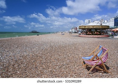 Brighton, UK - July 18, 2007: Deckchairs on beach on a Summer day in Brighton on the south coast of England.They are iconic of Brightons association with summer holidays dating back to the 1890s.