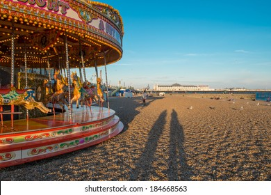 BRIGHTON, UK - July 27 2013: Two silhouettes of people standing next to a traditional carousel on Brightons famous beach as the sun goes down with the famous pier in the background.