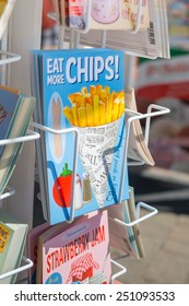 BRIGHTON, UK- JULY 28: Eat more chips postcard in a postcard rack on the seafront in Brighton, july 2013.