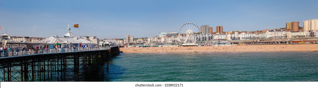 BRIGHTON, UK - JUN 5, 2013: Beachfront panoramic view with the Ferris Wheel promenade and shingle beach pictured from the Brighton Palace Pier on a sunny summer day
