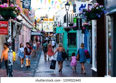 Brighton, UK - June 2018 People Walking Thru the Narrow Alley on Busy Day. Shops in The Lane in Brighton East Sussex United Kindom. Small Local Stores and Bunting for Attractions.