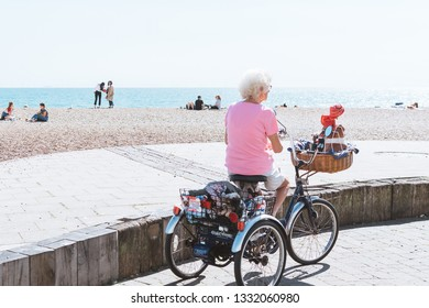 BRIGHTON / UK - June 22, 2018: An elderly woman standing against her tricycle
