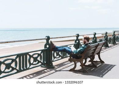 BRIGHTON / UK - June 22, 2018: A man sunbathing on the Brighton promenade