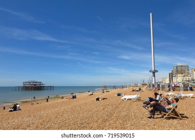 BRIGHTON, UK – MAY 21, 2017: People relax and sunbathe in deck chairs on Brighton's shingle pebble beach near the British Airways i360 observation tower and Brighton West Pier.