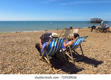 BRIGHTON, UK – MAY 21, 2017: An elderly man and woman read in deck chairs on Brighton's pebble beach overlooking windsurfers and Brighton West Pier in the English Channel.