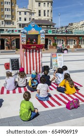 BRIGHTON, UK - MAY 31ST 2017: A group of children watching a traditional Punch and Judy puppet show on the seafront in Brighton, UK, on 31st May 2017.