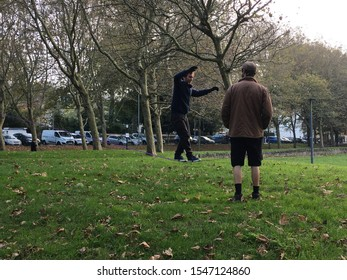 Brighton UK - October 2019 man practicing walking rope in park the Level with another man watching or coaching