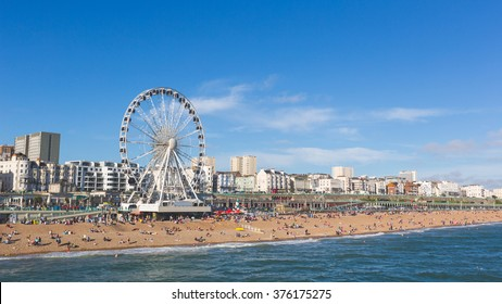 Brighton view of seaside from the pier. Panoramic shot with the famous ferris wheel, the stones beach with unrecognizable persons on a sunny summer day.