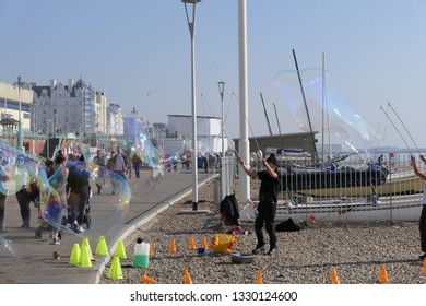 Brighton/East Sussex/England - February 27 2019: People enjoying the sun on Brighton seafront promenade watching bubble blowers during the hottest February on record in the UK