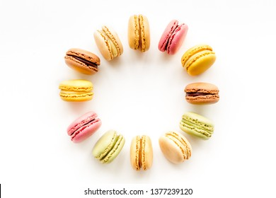 Brignt macarons for sweet break on white background top view frame